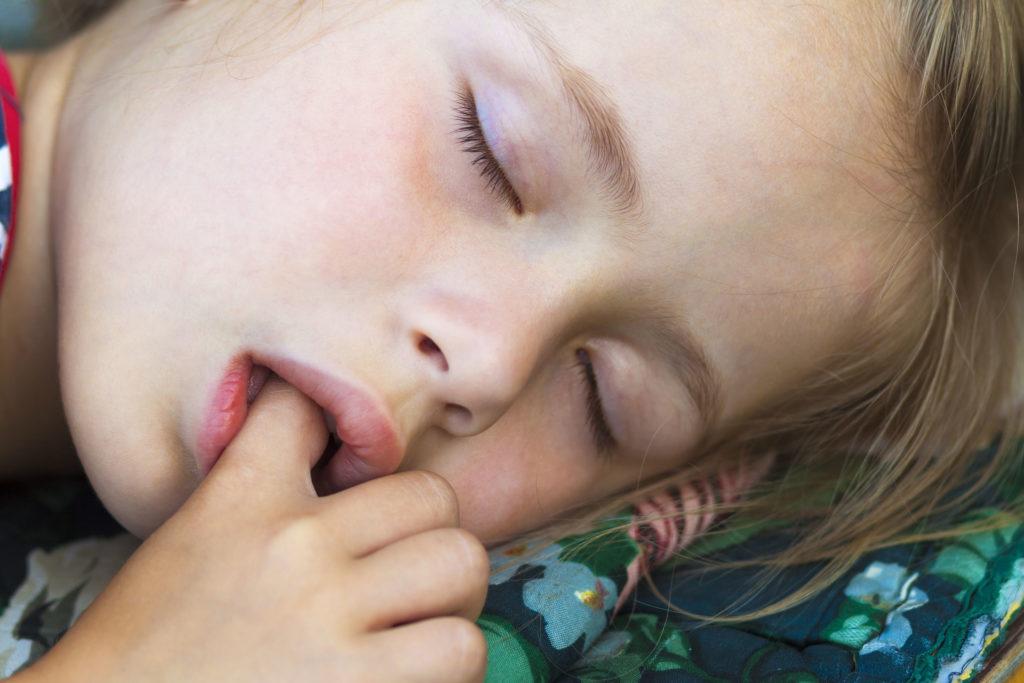 81343745 - little pretty girl sleeping, sucking thumb and